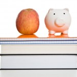 an apple and a piggy bank on top of a stack of books