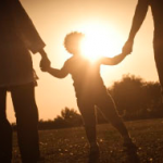 parents holding their child's hand while out in the sun