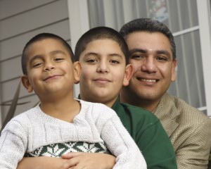 Latino father and two young sons sitting together in front of a house