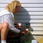 A woman taking a water sample from an outdoor home spigot.