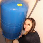 Young woman takes a water sample from a pressure tank