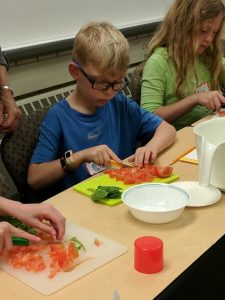 Young boy from the Fond du Lac County Junior Master Gardener program slicing vegetables