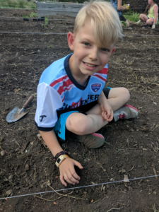 picture of a blonde hair boy sitting in the garden