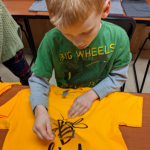 Ablonde haired boy making a bee kind t-shirt.