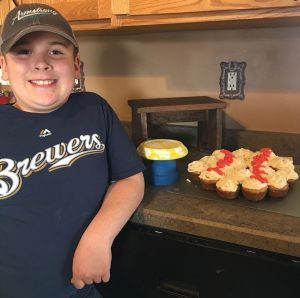 4-H member with blue Brewers shirt displaying his projects.